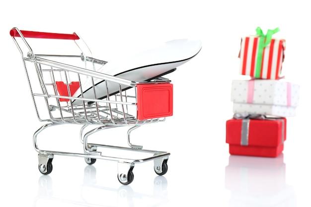 Kleiner einkaufswagen mit computermaus und geschenkboxen isoliert auf weißer oberfläche