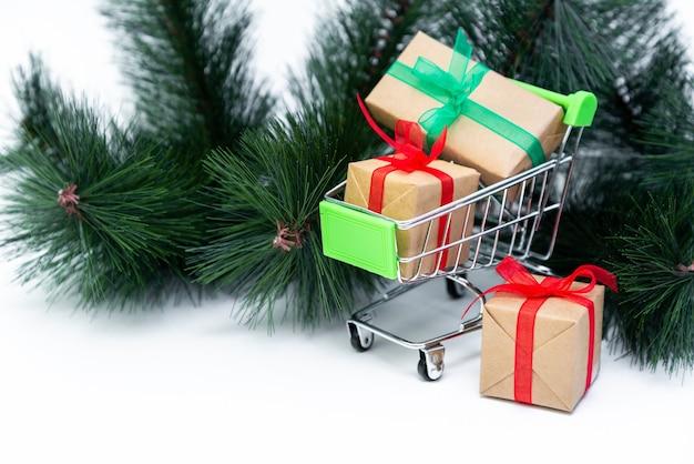 Kleiner einkaufswagen mit geschenkboxen auf weißer oberfläche mit weihnachtsbaum. online einkaufen