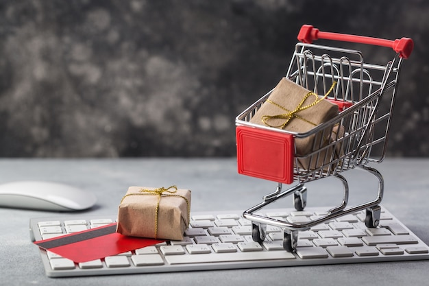 Kleiner einkaufswagen mit geschenken und kreditkarte auf konzepten einer laptoptastatur