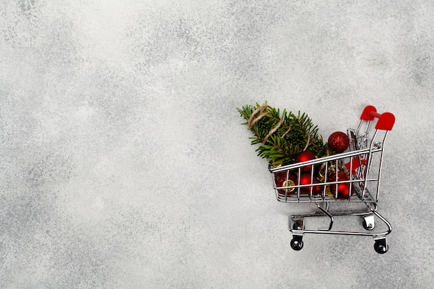 Kleiner einkaufswagen mit weihnachtsschmuck isoliert