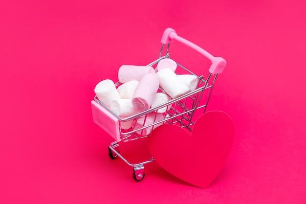 Kleiner einkaufswagen voller süßer marshmallow-bonbons. geben sie geschenke mit liebe am valentinstag und