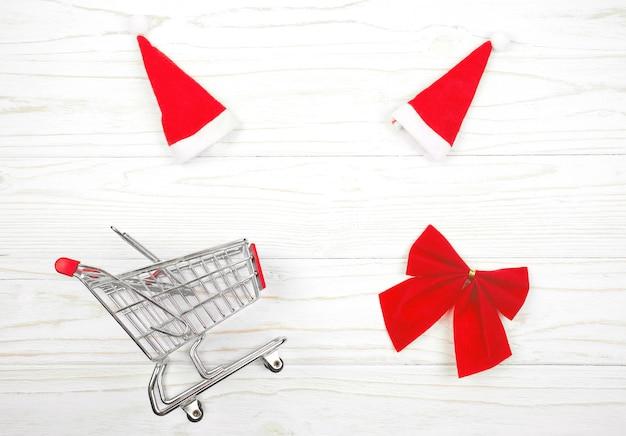 Kleiner einkaufswagen, weihnachtsmützen und eine rote weihnachtsschleife