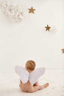 Kleiner engel, der wolken und sterne betrachtet.