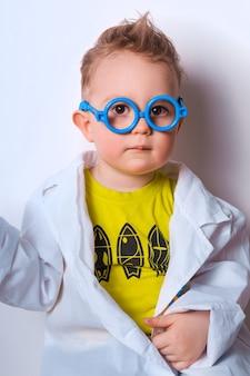 Kleiner entdecker junge spielt wissenschaftler lustiges kind mit blauer brille nettes buntes foto doktor