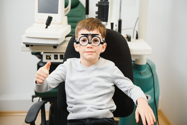 Kleiner ernster junge, der auf stuhlbüro des sehtests sitzt. der arzt nimmt die linsen für eine spezielle brille auf