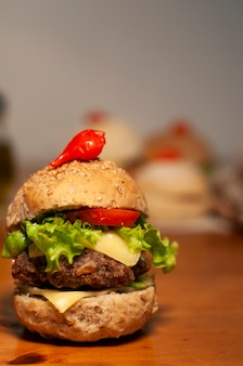 Kleiner feinschmeckerhamburger mit flockigen sandwichen im hintergrund