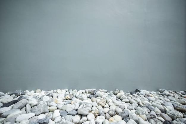Kleiner felsen mit grauem wand- und kopienraum für hintergrund.