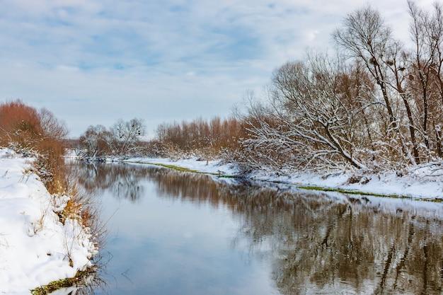 Kleiner fluss im winter am sonnigen tag gegen bewölkten himmel. land winterlandschaft
