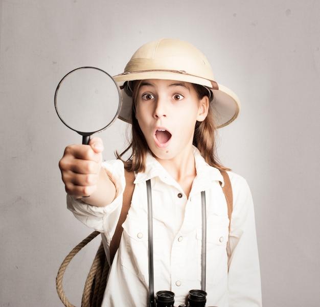 Kleiner forscher, der durch lupe schaut