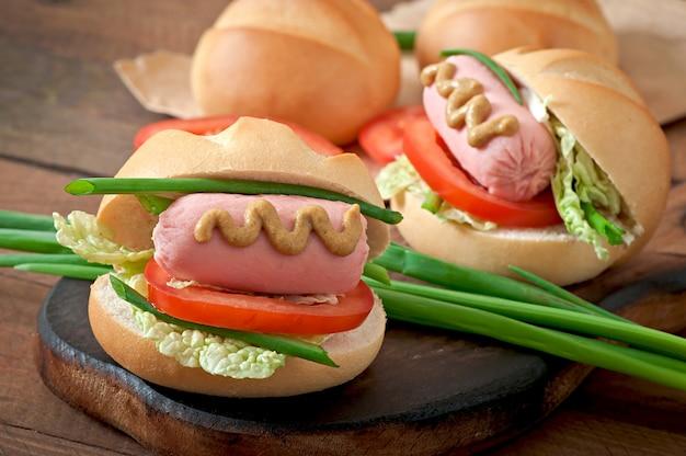 Kleiner fröhlicher hot dog mit wurst und tomate