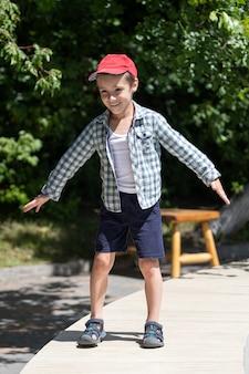 Kleiner fröhlicher junge in sommershorts und einem hemd spielt und zeigt das flugzeug mit seinen händen auf dem hintergrund