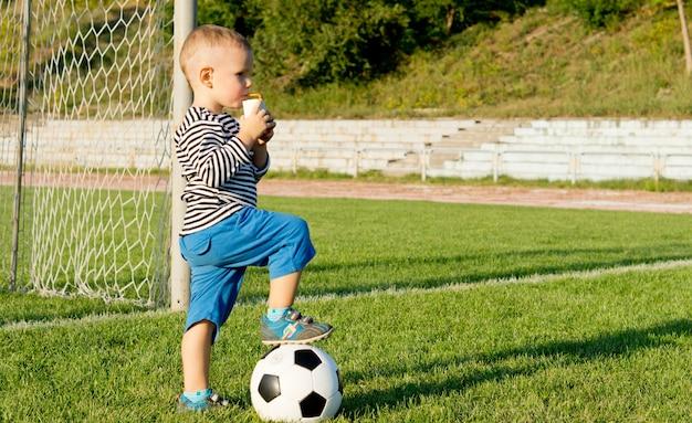 Kleiner fußballspieler, der mit dem fuß auf dem ball steht und im abendlicht saft trinkt, während er eine spielpause einlegt