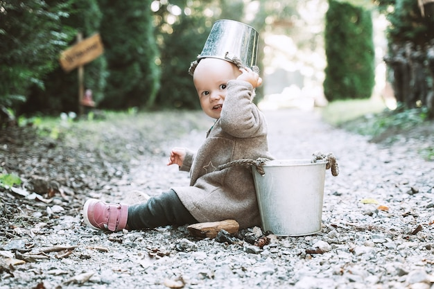 Kleiner gartenhelfer kind spielt mit eimern im garten oder auf forstweg