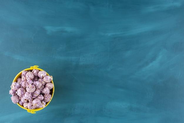 Kleiner gelber eimer gefüllt mit lila popcorn-süßigkeiten auf blauem hintergrund. foto in hoher qualität