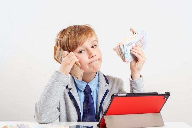 Kleiner geschäftsmann, der durch smartphone spricht. junge hält geld. zukünftige ausbildung, beruf.