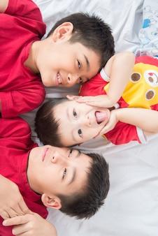 Kleiner geschwisterjunge legte sich auf dem bodenblick auf die kameraliebe nieder und glücklich