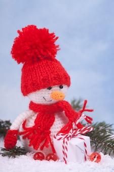 Kleiner gestrickter schneemann ein neujahrsgeschenk, ein symbol des jahres. weihnachtsdekoration.