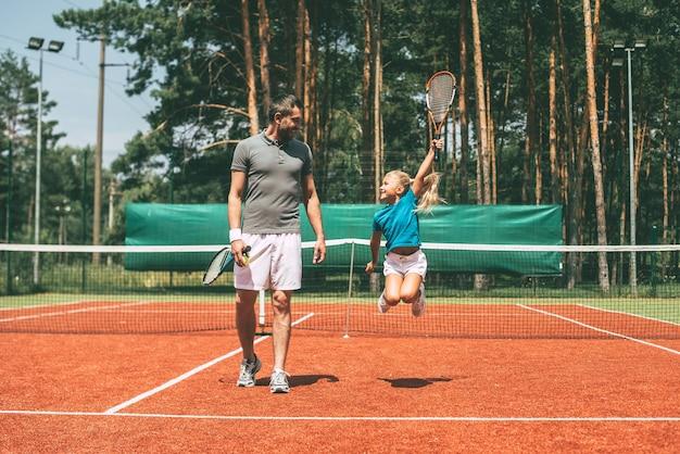 Kleiner gewinner. volle länge des kleinen blonden mädchens in sportkleidung, das tennisschläger trägt und ihren vater ansieht, der in ihrer nähe durch den tennisplatz geht?
