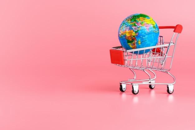Kleiner globus in einem einkaufswagen auf rosa hintergrund