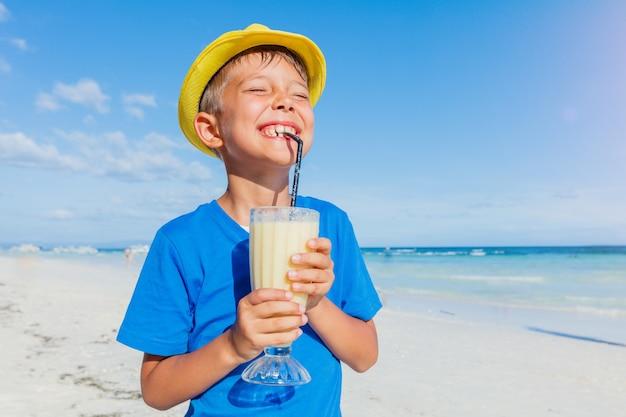 Kleiner glücklicher junge, der bananencocktail am tropischen strand trinkt
