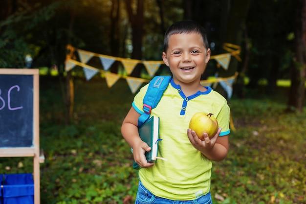 Kleiner glücklicher junge mit rucksack und notizblock. zurück zur schule. das konzept der bildung, der schule