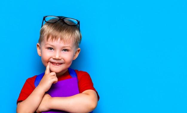 Kleiner glücklicher lächelnder junge mit gläsern auf seinem kopf, buch in den händen, schultasche auf seinen schultern. zurück zur schule. bereit zur schule