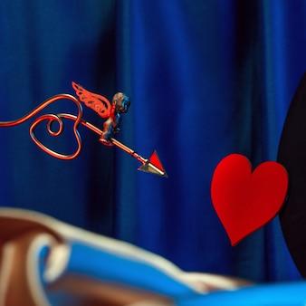 Kleiner goldener amor markiert sein ziel mit einem pfeil im herzen, valentinstagskonzept.