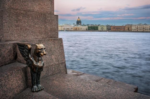 Kleiner greif am ufer der universität und blick auf die isaakskathedrale über die newa in st. petersburg