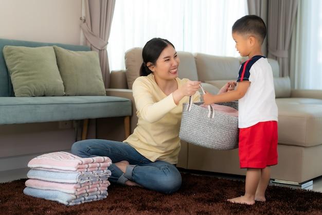 Kleiner helfer der schönen asiatischen mutter und des kinderjungen haben spaß und lächeln, während sie ihrer mutter helfen, gefaltete kleidung zu hause zu waschen. glückliche familie.