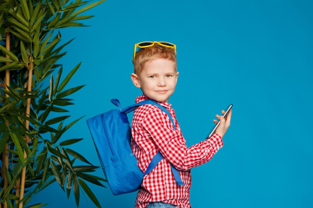 Kleiner hippie-junge mit dem rucksack und sonnenbrillen, die telefon halten