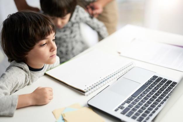 Kleiner hispanischer junge, der konzentriert aussieht, dem lehrer während des online-unterrichts für kinder zuhört und mit seinem zwillingsbruder zu hause am tisch sitzt. selektiver fokus