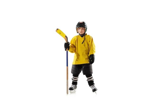 Kleiner hockeyspieler mit dem stock auf eisplatz und weißer studiowand