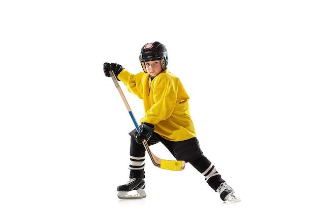 Kleiner hockeyspieler mit dem stock auf eisplatz und weißer wand