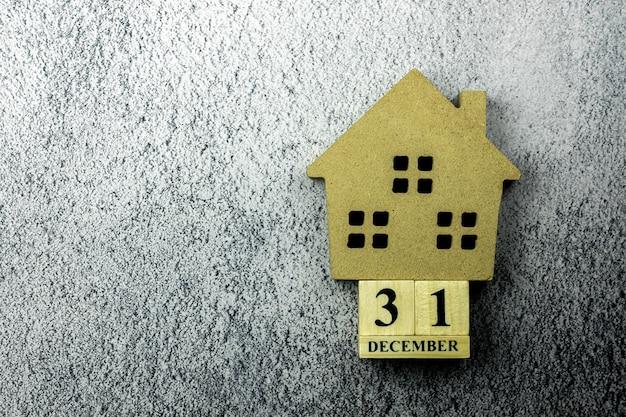 Kleiner home-modus und ein vintage-holzkalender am 31. dezember auf betonboden.