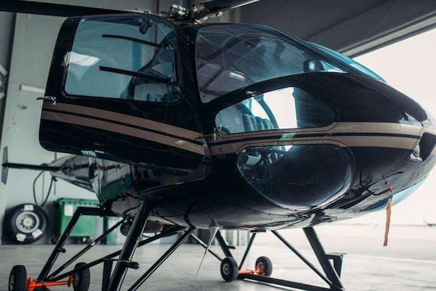 Kleiner hubschrauber im hangar, hubschrauber einer privaten fluggesellschaft
