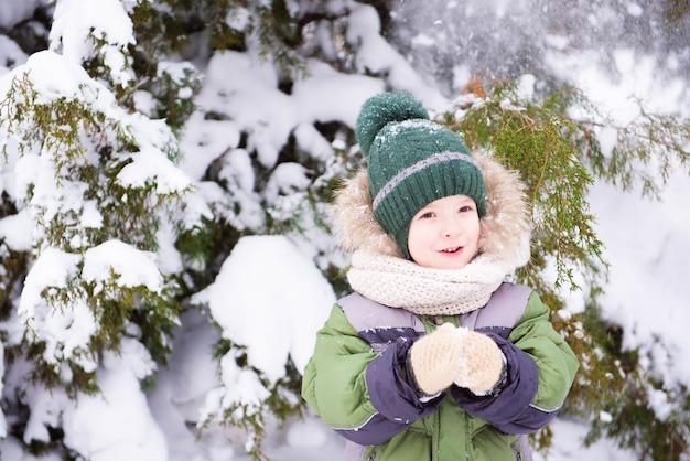 Kleiner hübscher junge spielt mit schnee im park. weihnachtsstimmung