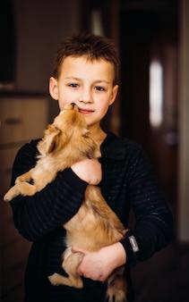 Kleiner hund leckt das gesicht des jungen, während er es auf seinen armen hält