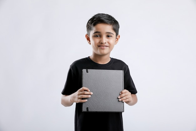 Kleiner indischer / asiatischer junge, der notizbuch zeigt
