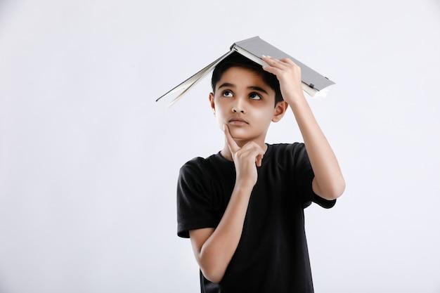Kleiner indischer / asiatischer junge mit buch auf dem kopf und ernsthaftem denken