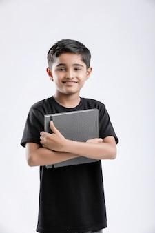 Kleiner indischer / asiatischer junge mit notizbuch