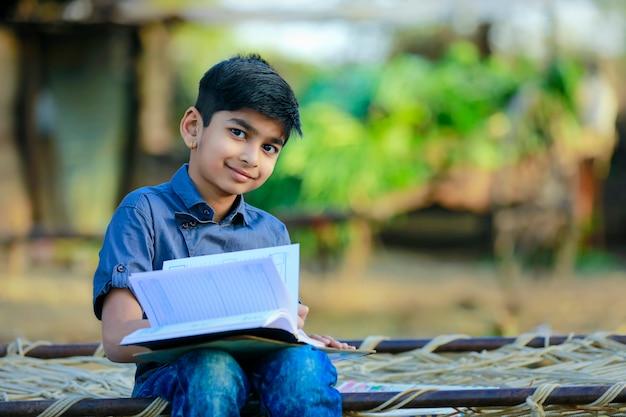 Kleiner indischer junge, der zu hause studiert