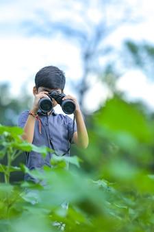 Kleiner indischer junge genießt in der natur mit fernglas