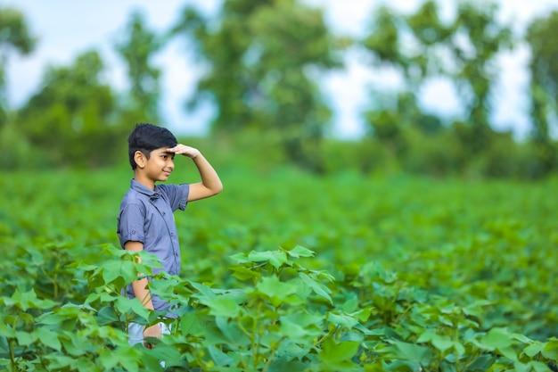 Kleiner indischer junge genießt in der natur und sucht etwas Premium Fotos