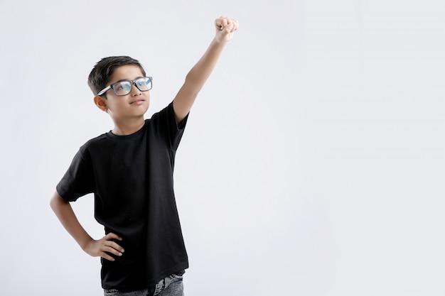 Kleiner indischer junge in einer superman-pose