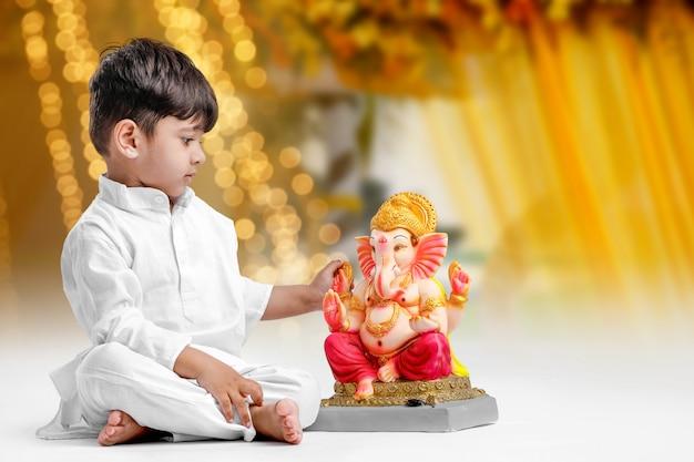 Kleiner indischer junge mit lord ganesha, der ganesh festival feiert
