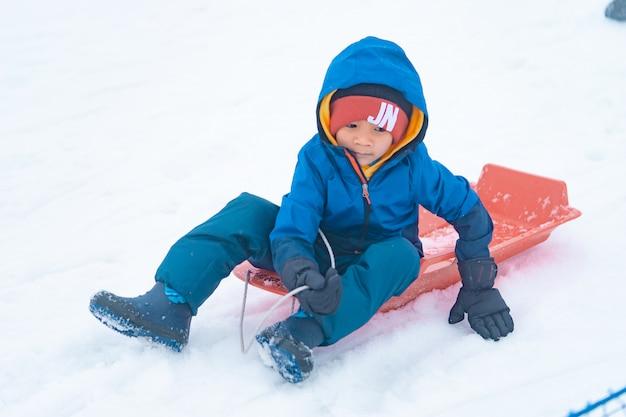 Kleiner japanischer junge rutscht den schneeschlitten im skigebiet gala yuzawa hinunter