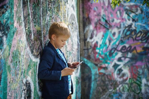 Kleiner junge absorbiert in seine tablette.