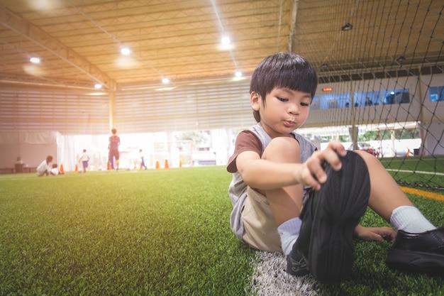 Kleiner junge ändert seine schuhe, die zum fußballspiel fertig werden