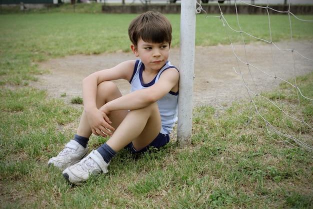 Kleiner junge allein auf dem fußballplatz