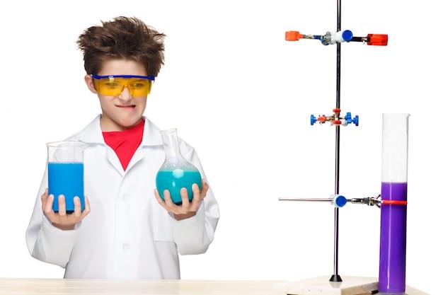 Kleiner junge als chemiker, der experiment mit chemischer flüssigkeit im labor tut